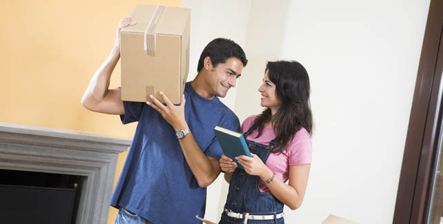 Couple packing boxes prepares to move their things to self storage