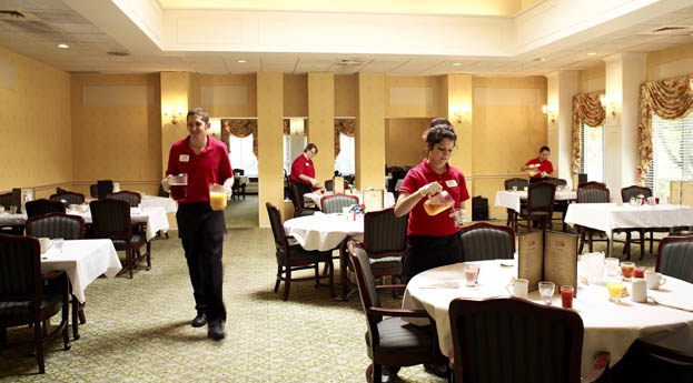 Dining room servers at senior living in Roseville prepare for the latest meal