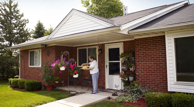 A resident waters flowers in the villas at senior living in Dearborn Heights, MI