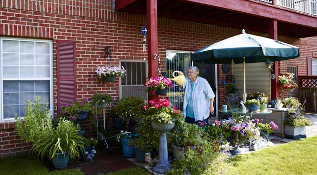 Tend to plants on the balcony or patio at senior apartment in Riverview