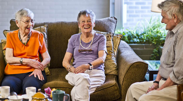 Residents enjoy socializing in the lobby at senior living in Royal Oak