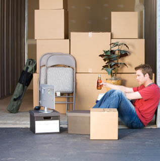 man relaxing in storage unit after unloading boxes