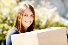 Young woman carrying a moving box at our Maple Grove storage units