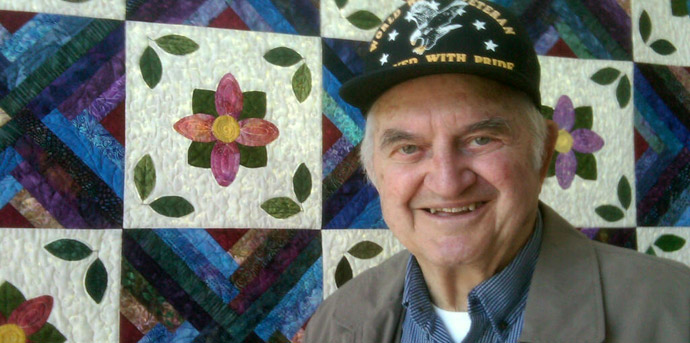 Davenport ia senior living resident in front of quilt