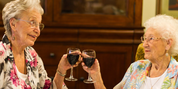 Residents toasting at their riverside senior living community