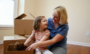 mother and daughter packing boxes for a move