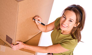 woman labeling cardboard boxes for self storage
