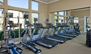 Workout room with mirrors at apartments in Riverside
