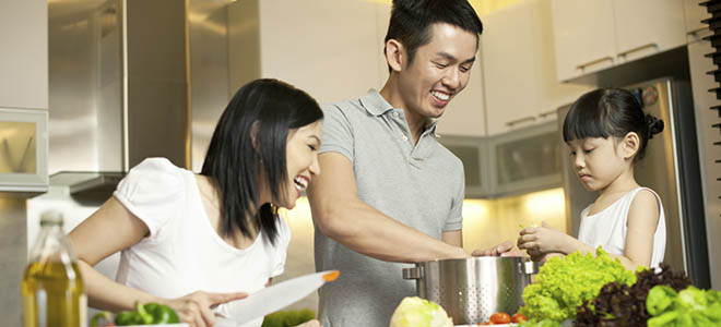 A happy family cooks a meal together at their apartments in Northville