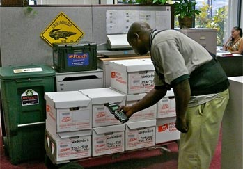 Pouch Records Management employee picks up boxes to deliver.