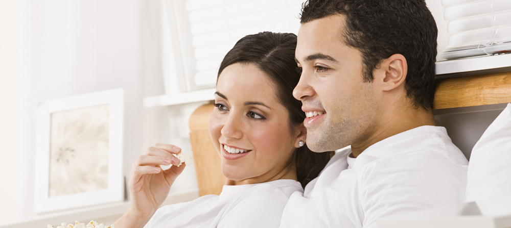 Happy couple watches a movie at apartments