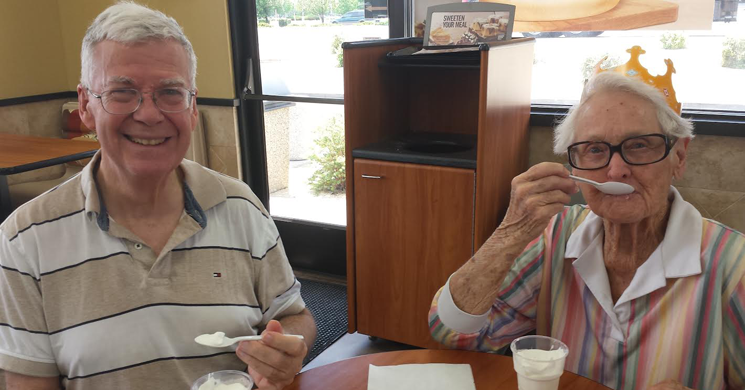 Elder couple eating yogurt