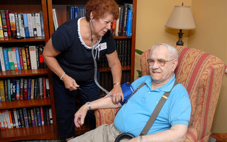 Employee checking blood pressure in Boyertown senior living