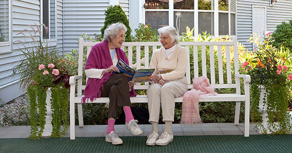 Assisted living friends share a moment on a bench at senior living facility in Manchester Center, VT.