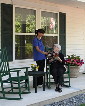 Windham NH senior living resident reading on the porch.