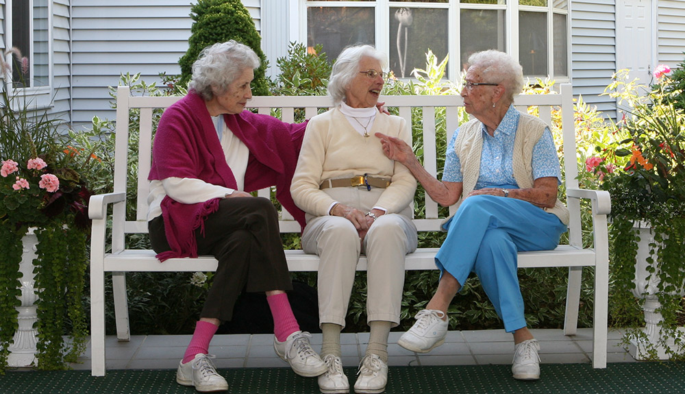 Three friends on a bench at assisted living in Manchester Vermont