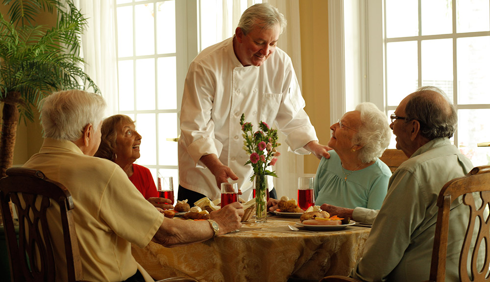 Chef presenting a fine meal to seniors at Woodstock Terrace in Woodstock, VT.