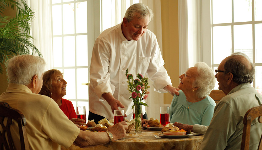 Chef presenting a fine meal to seniors at Scarborough Terrace in Scarborough, ME.