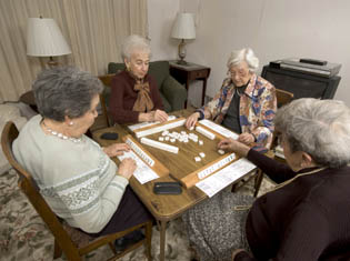 Happy residents enjoying board games at Green Leaf Care Center