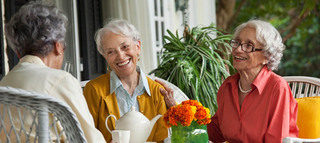 Three women at table enjoying senior living