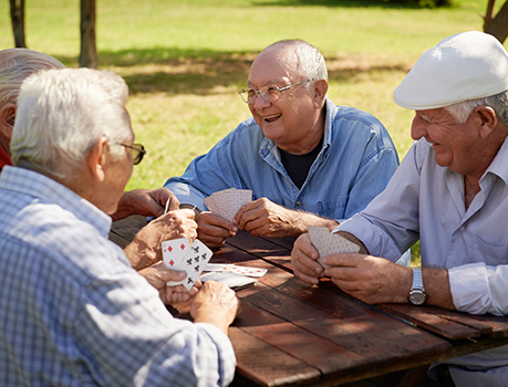Senior friends at assisted living in Strasburg, VA play a friendly game of cards.
