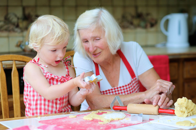 Little girl and senior woman baking
