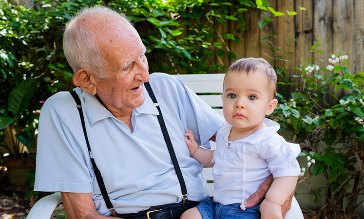 Dodge City senior living shows grandpa and grandkid relaxing on a bench