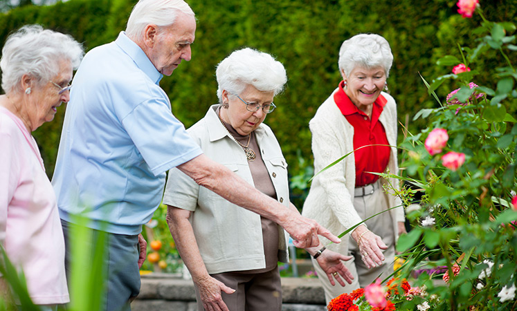 Residents looking at flowers at the senior living in Olathe