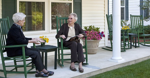 Assisted living friends share a moment on a bench at senior living facility in Windham, NH.