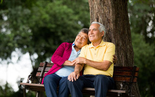 Senior couple on a bench at the park enjoying nature