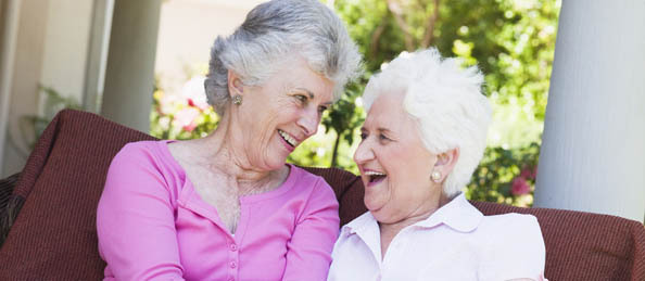 Senior women embrace and laugh Charlton Place Assisted Living