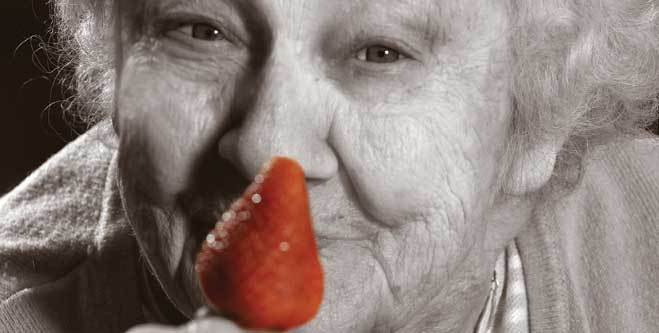 Resident at dementia care community with strawberry