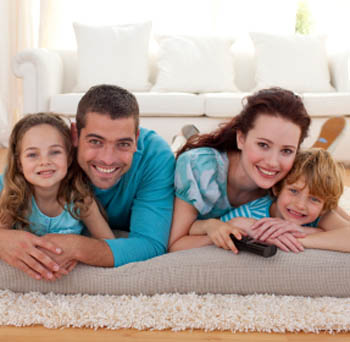 Family of four laying in living room Singh Management