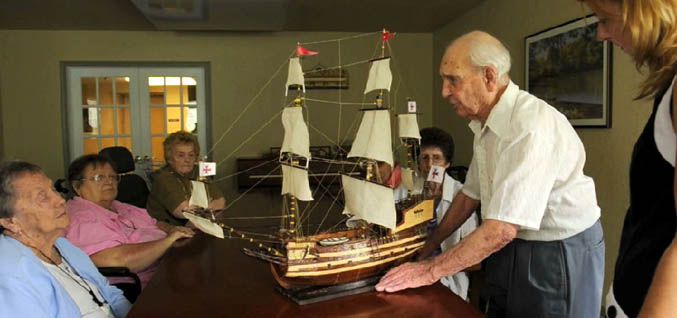 Seniors with model ship American House Senior Living