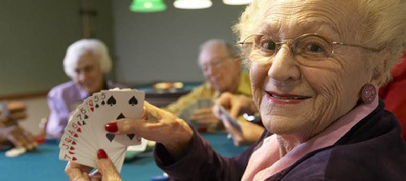 Senior woman playing cards during a Glenn Park Senior Living social event