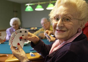 Woman playing cards at a Chancellor Senior Management community