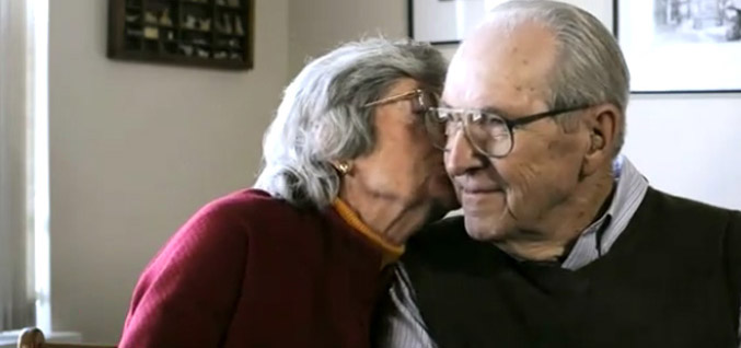 Couple sitting on couch kissing American House Senior Living