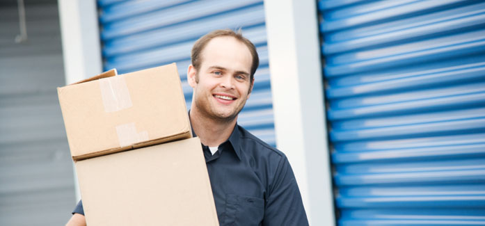 Man carrying boxes to store at Self Storage Plus