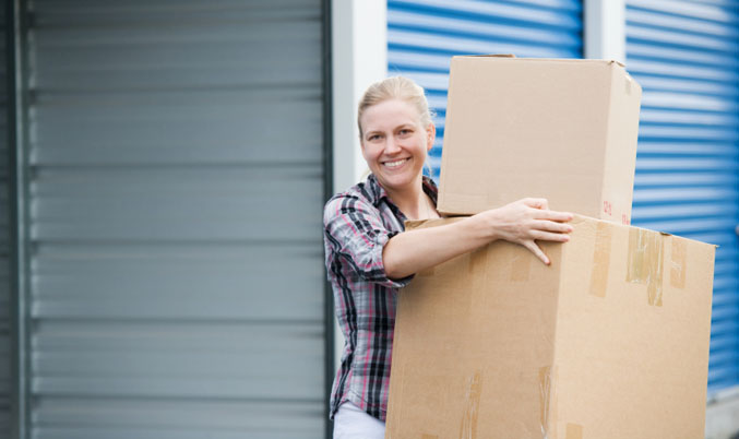 Woman holding boxes outside unit Our Self Storage Facilities