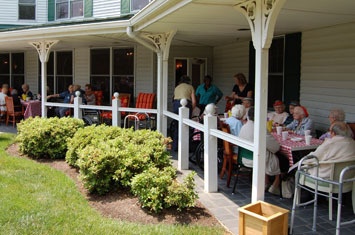 Senior residents relaxing on porch at Chelsea Senior Living Tinton Falls