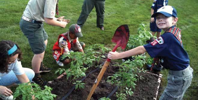 Kids planting in garden of a senior retirement community
