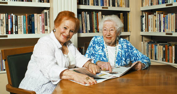 Female senior residents in library at Aston Gardens at Parkland Commons retirement community in Parkland