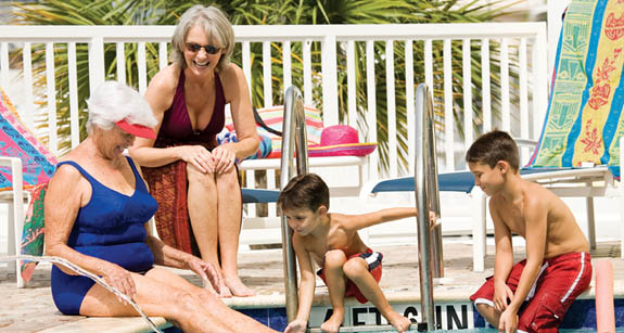 Grandma with kids in pool at Aston Gardens at Sun City Center retirement community