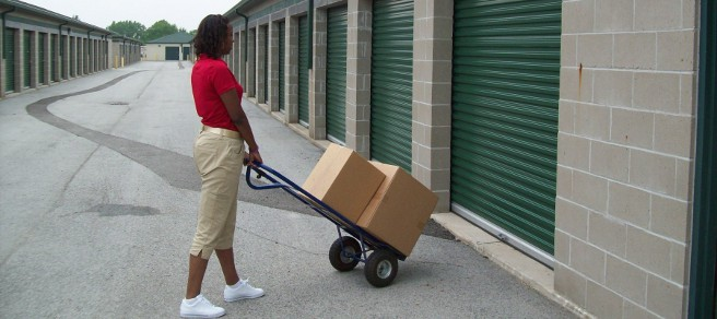 Woman loading boxes with hand truck Mini Storage Depot