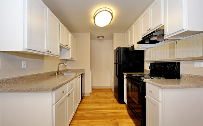 Upgraded Kitchens with black appliances and wood flooring